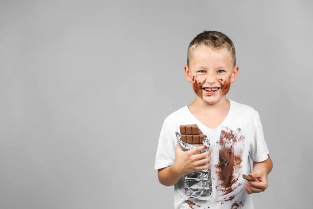 Kleiner Junge hält eine Tafel Schokolade in der hand – Foto