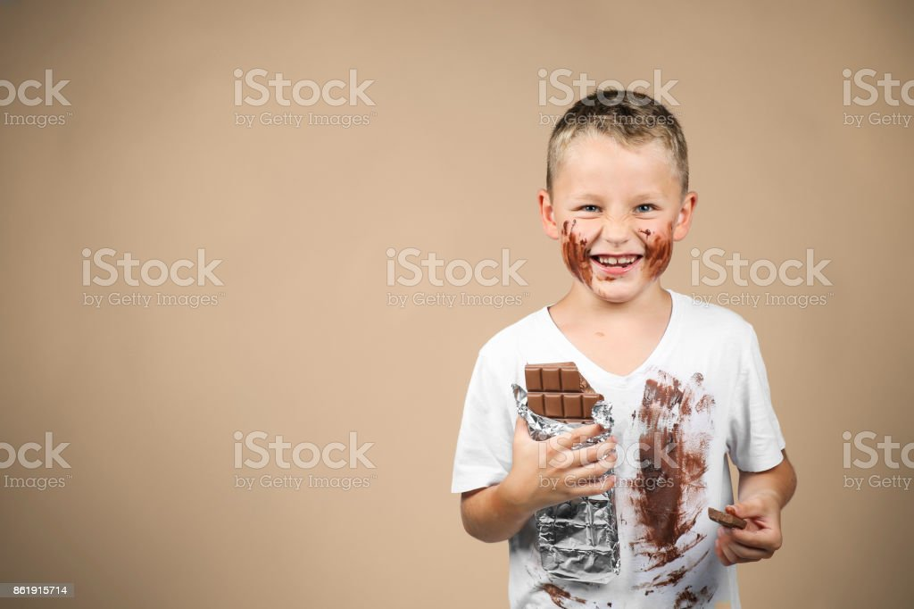 Little boy holds a bar of chocolate in his hand stock photo