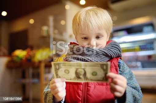 Little boy holds a one-dollar currency note. Kids and money concept. Training in handling money.