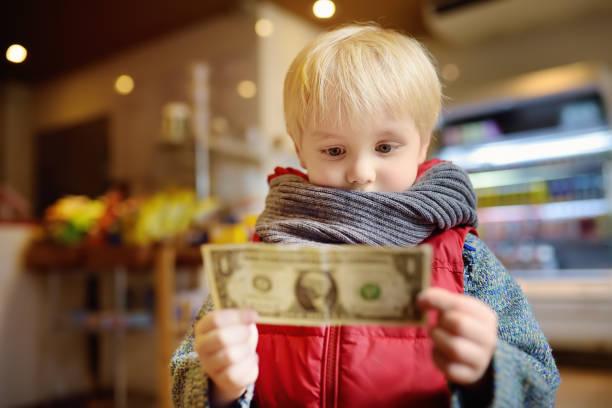 Niño tiene una nota de la moneda de un dólar. - foto de stock