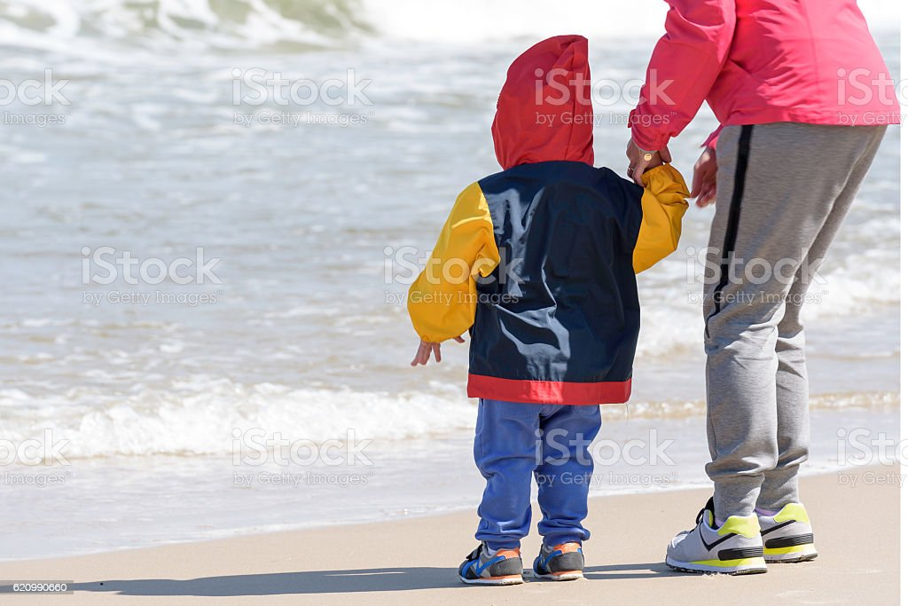 Little boy holds his mother hand and watches the waves foto royalty-free