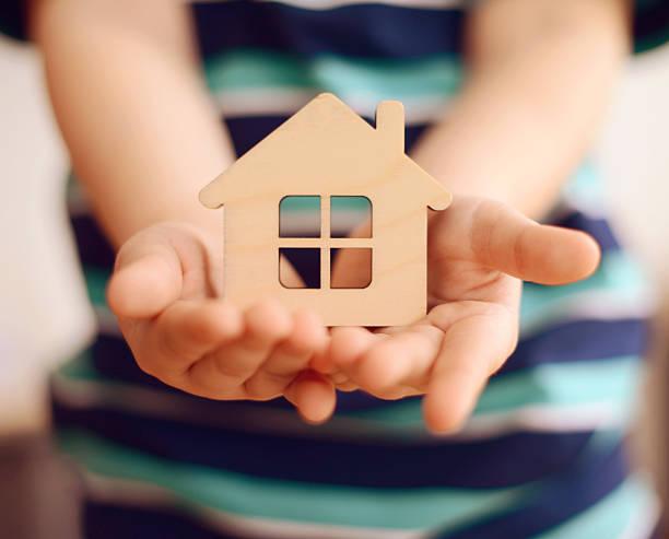 Kleiner Junge hält kleine Spielzeug Haus in Händen – Foto