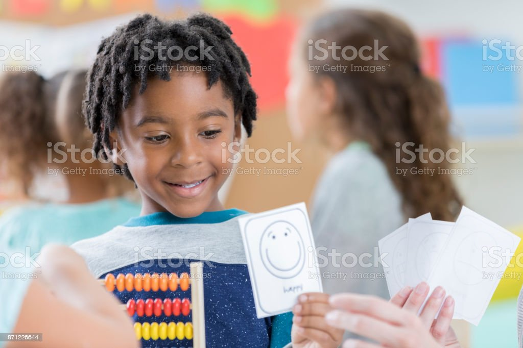 Little boy holds smiley face card at school stock photo
