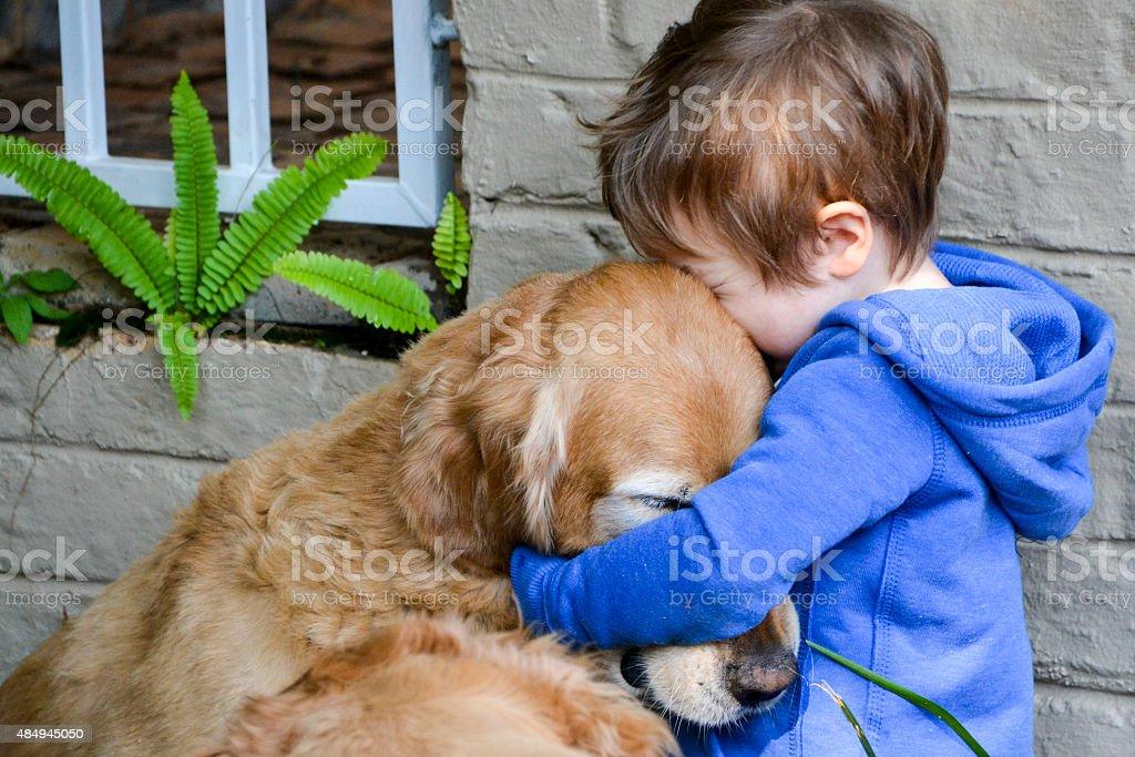 Little Boy Hugging His Dog - Golden Retriever stock photo