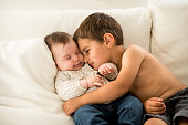 Young boy embracing his baby sister taking care about her.