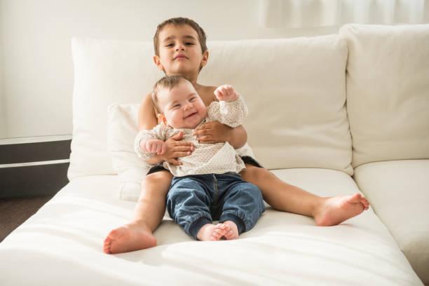 kleiner junge umarmt sein jüngeres geschwisterchen - kemter stock-fotos und bilder
