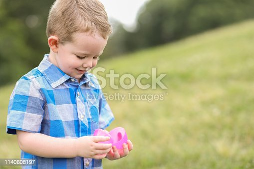Little boy hunting Easter eggs at a local park.  He happily opens an egg that he found.
