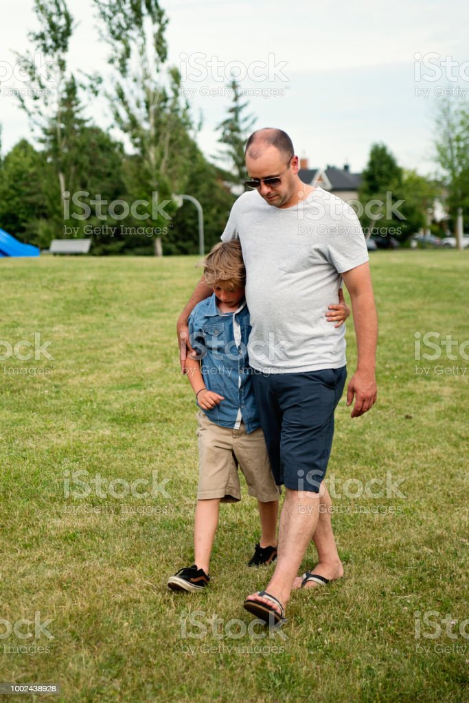 Little boy hurting being comforted by adult in suburb park. stock photo