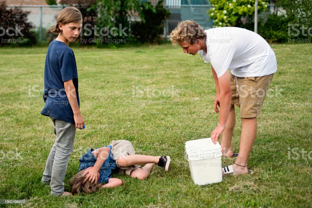 Little boy hurting curled on the grass in suburb park. stock photo