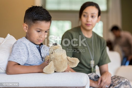 Elementary age boy plays with a stuffed animal, ignoring his mom who is about to leave for a military assignment.