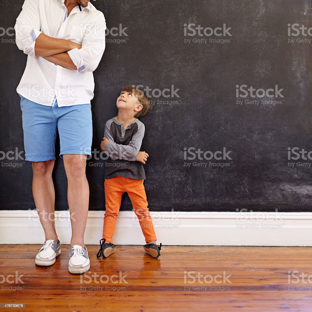 Little boy imitating his father's pose stock photo