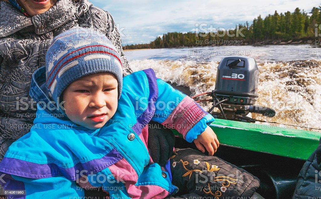 Little boy in a boat on  river in Western Siberia stock photo