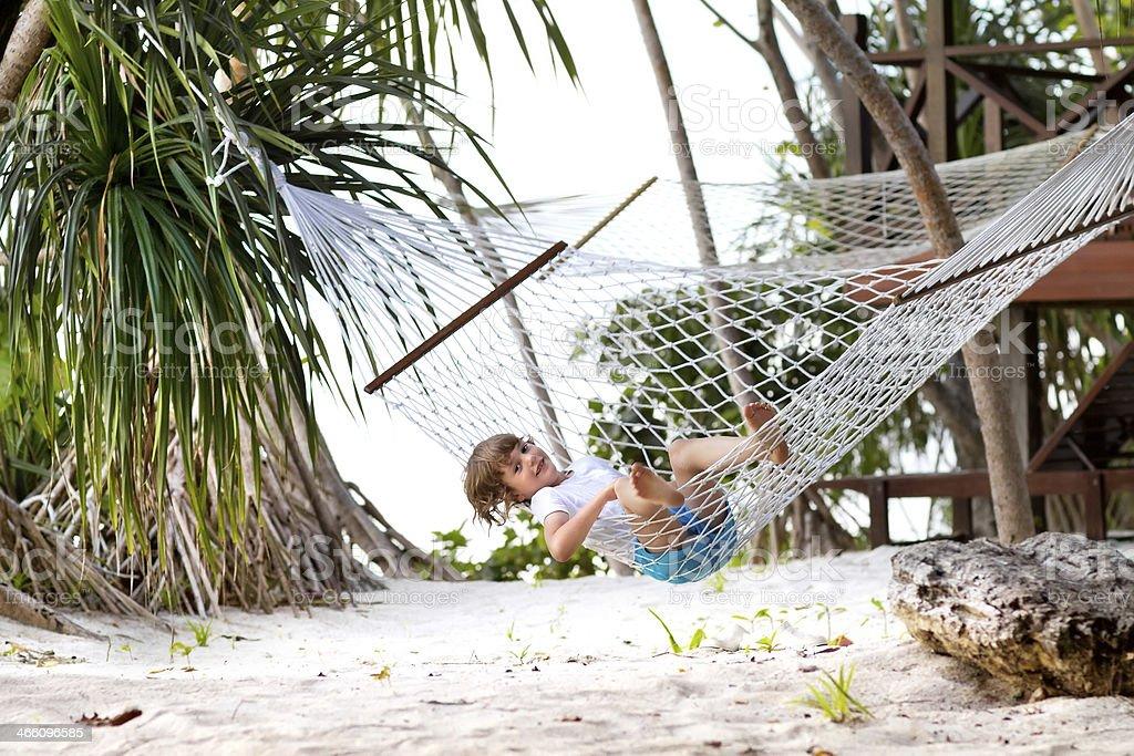 Little boy in a hammock on tropical beach royalty-free stock photo