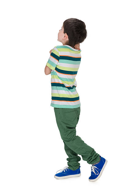 Little boy in a striped shirt looks back stock photo