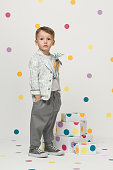little boy in the trendy and designer suits and sneakers on a white background