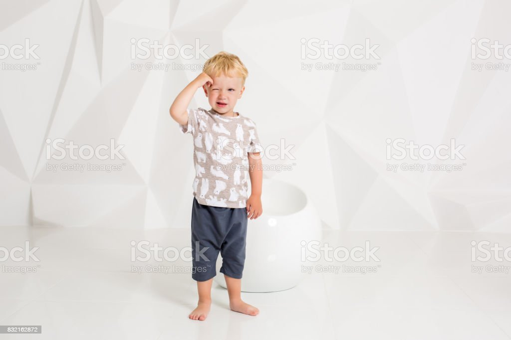 little boy in a t-shirt and shorts on a white background stock photo
