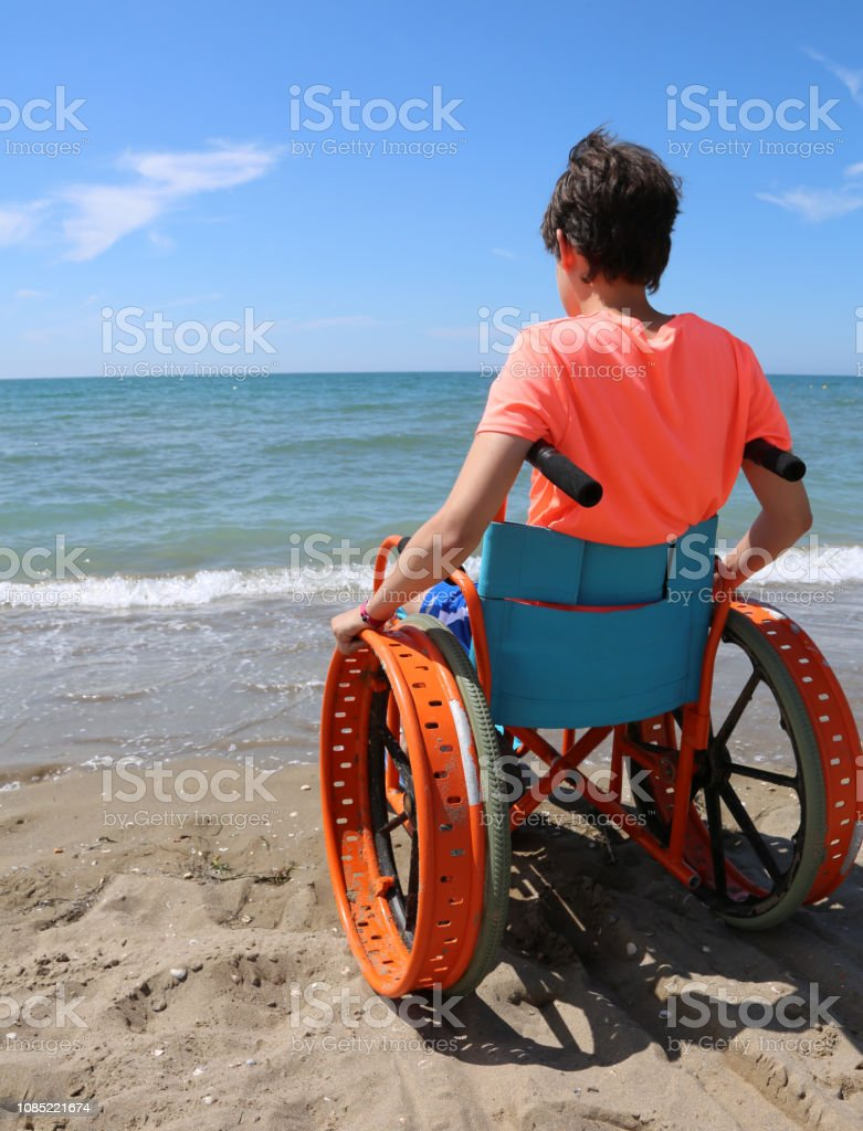 little boy in a wheelchair looks at the sea from the beach stock photo
