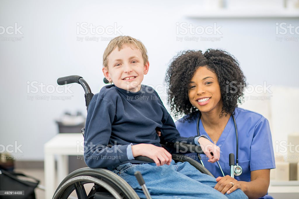 Little Boy in a Wheelchair with A Nurse stock photo