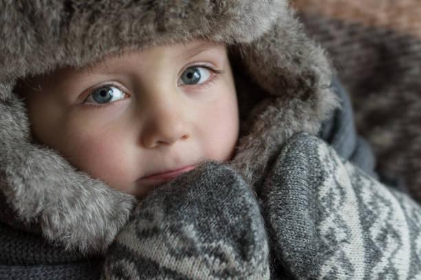 ein kleiner junge in einer wintermütze - strickmantel stock-fotos und bilder
