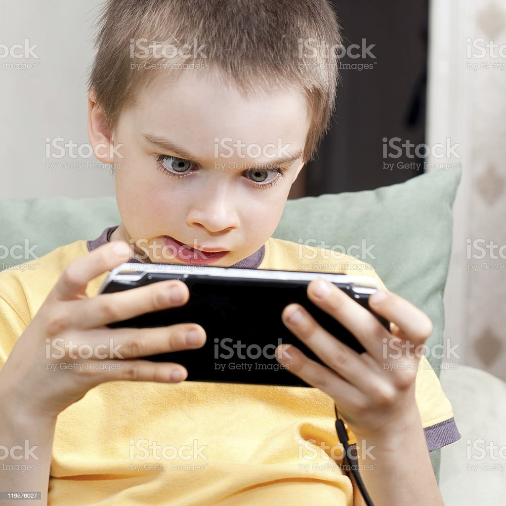 A little boy in a yellow shirt playing on his portable game royalty-free stock photo