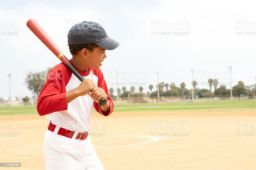 Little boy in baseball uniform practicing his swing stock photo