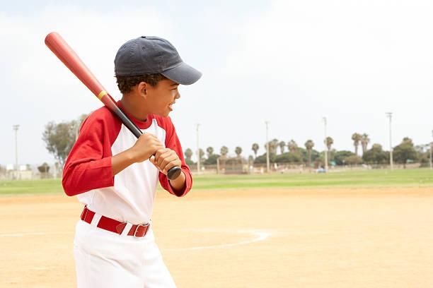 Little boy in baseball uniform practicing his swing stock photo