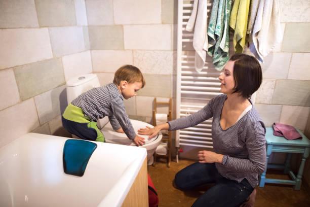 kleiner junge im badezimmer, die spülung der toilette, schöne mutter, ihm zu helfen - kinder wc stock-fotos und bilder