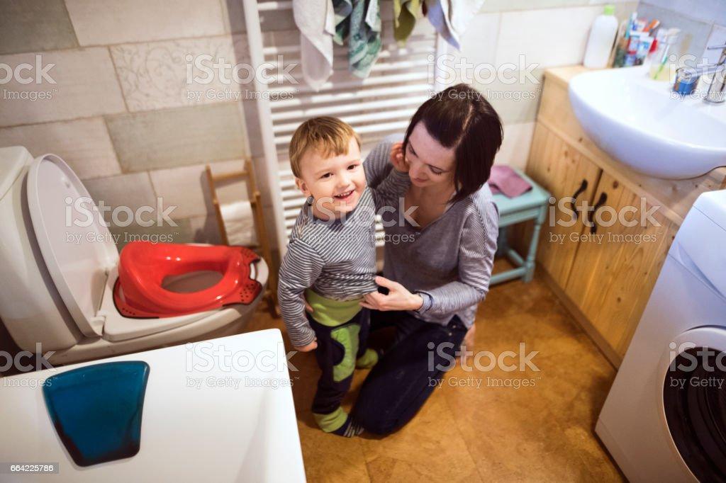 Kleiner Junge im Badezimmer neben der Toilette, schöne Mutter putzt ihn – Foto
