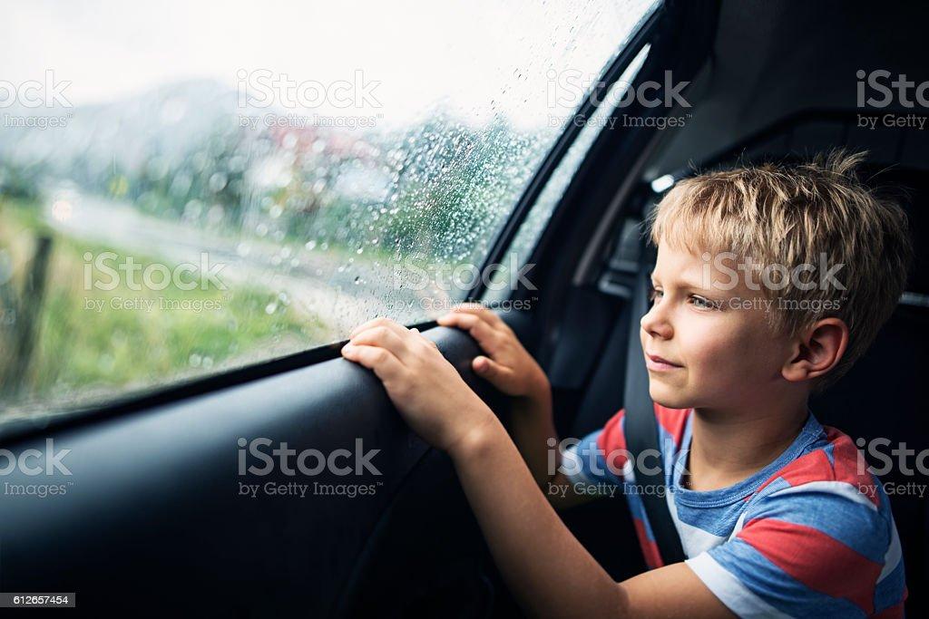 Little boy in car on rainy day - foto de stock