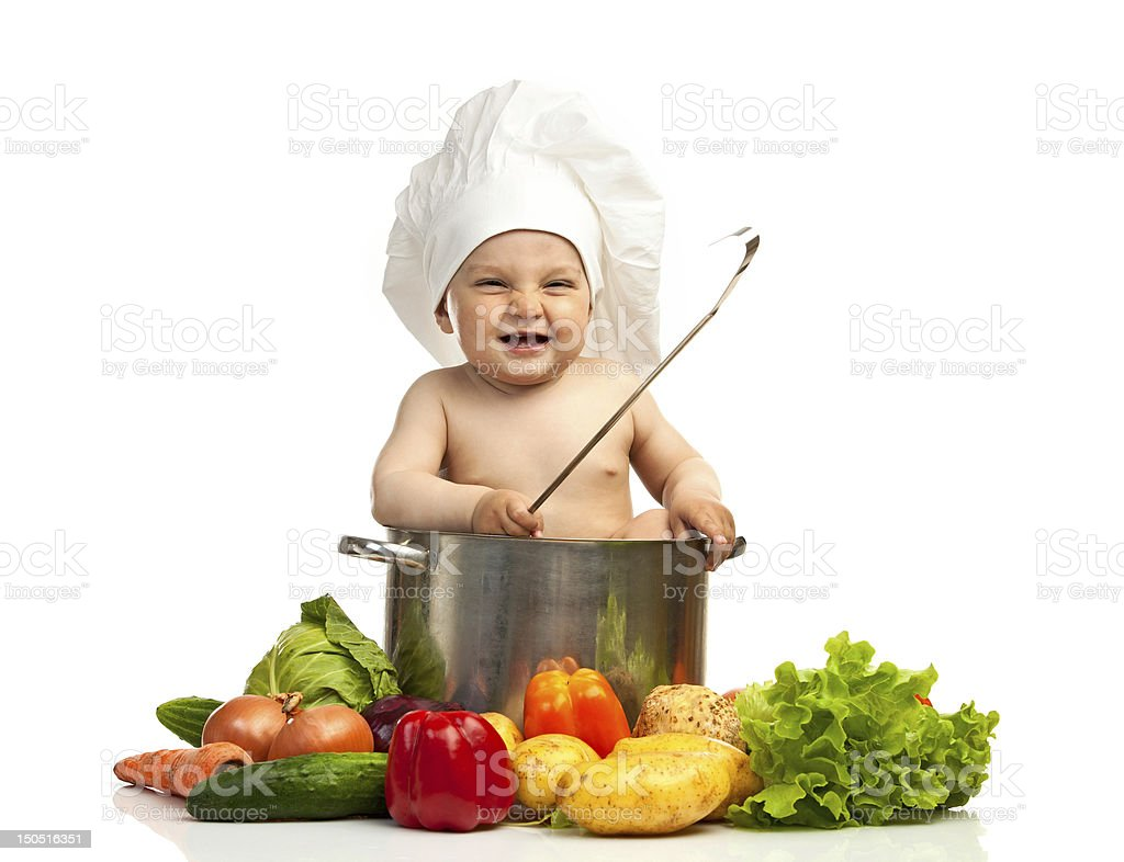 Little boy in chef's hat with ladle, casserole, and vegetables stock photo