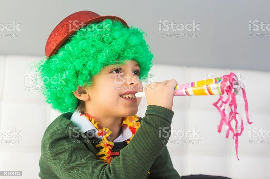 Little boy in clown wig having fun celebrating carnival stock photo