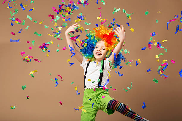 little boy in clown wig jumping and having fun - school fete stock photos and pictures