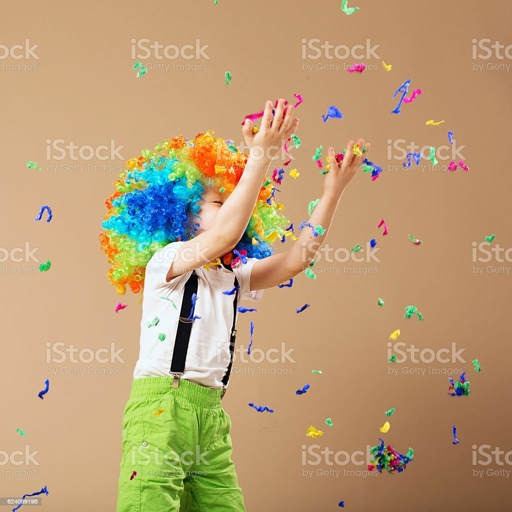 Little boy in clown wig jumping and having fun stock photo