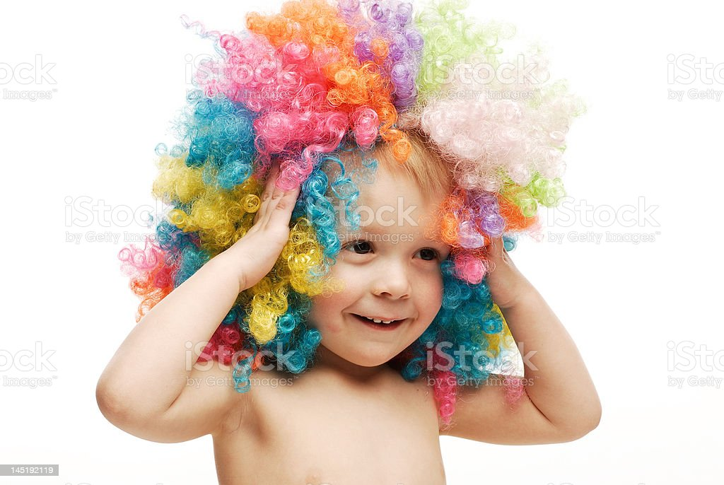 Little boy in colorful bright wig holding his head laughing royalty-free stock photo