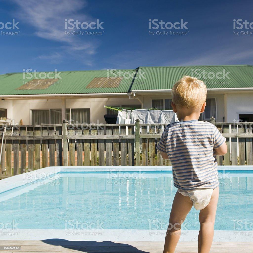 Little Boy in Diaper Looking at Backyard Pool stock photo