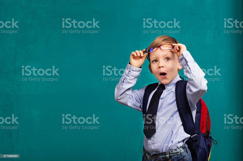little Boy in eyeglasses with big backpack stock photo