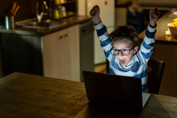 Little boy in front of his laptop screaming of joy