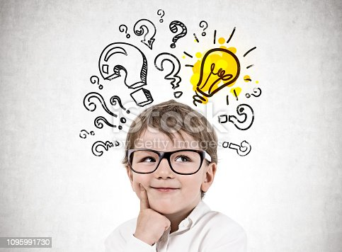 Adorable blond little boy wearing glasses and thinking standing near concrete wall with many question marks and lightbulb. Concept of idea