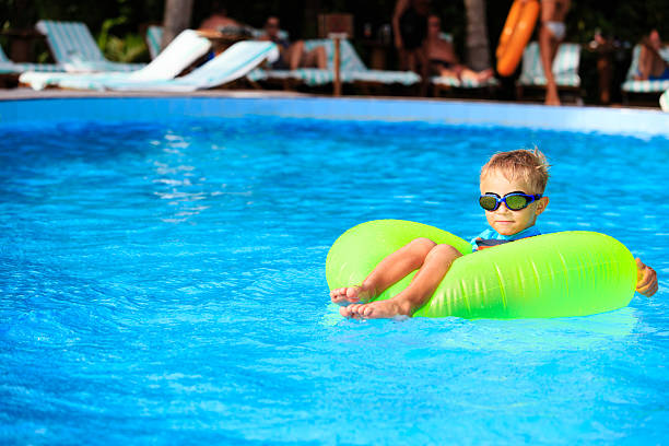 little boy in life ring fun at the swimming pool stock photo