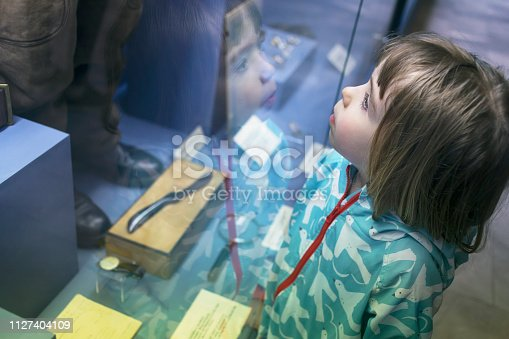 Little boy looking through museum display window.. Reflection in the glass.