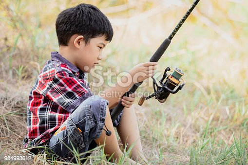 Asian young cute little boy sitting fishing in natural