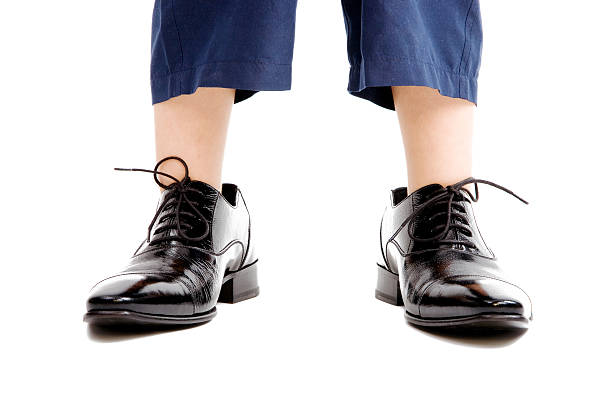 Little boy in oversize shoes stock photo