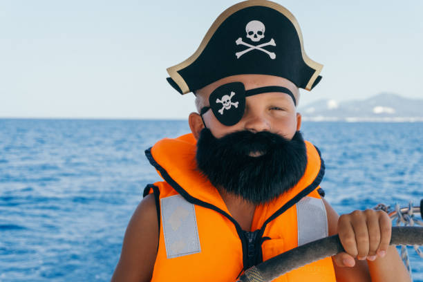 Little boy in pirate costume steering yacht Boy wears pirate costume with eye patch and hat and steering sailboat costume eye patch stock pictures, royalty-free photos & images