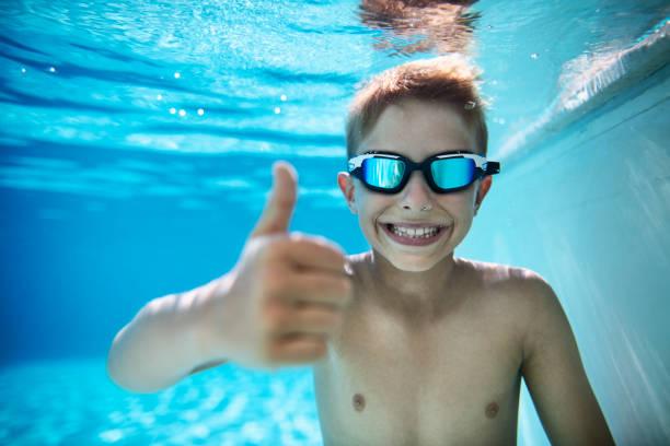 Kleiner Junge im Pool zeigt Daumen hoch – Foto