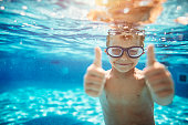 Little boy aged 6 swimming underwater. The boy is smiling at the camera showing thumbs up.\n