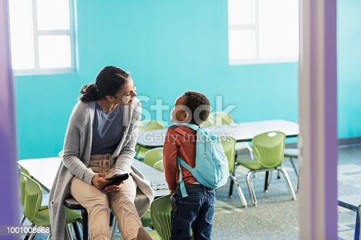 A little 4 year old African-American boy standing in his preschool classroom, talking to his teacher. The young woman, in her 20s, mixed race African-American and Caucasian, is sitting on a table, smiling at him.