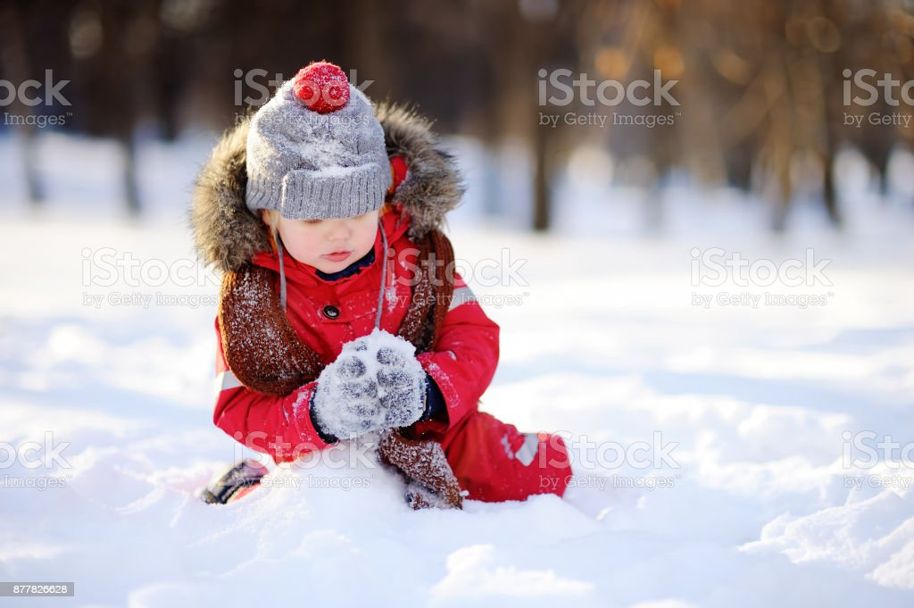Little boy in red winter clothes having fun with snow stock photo