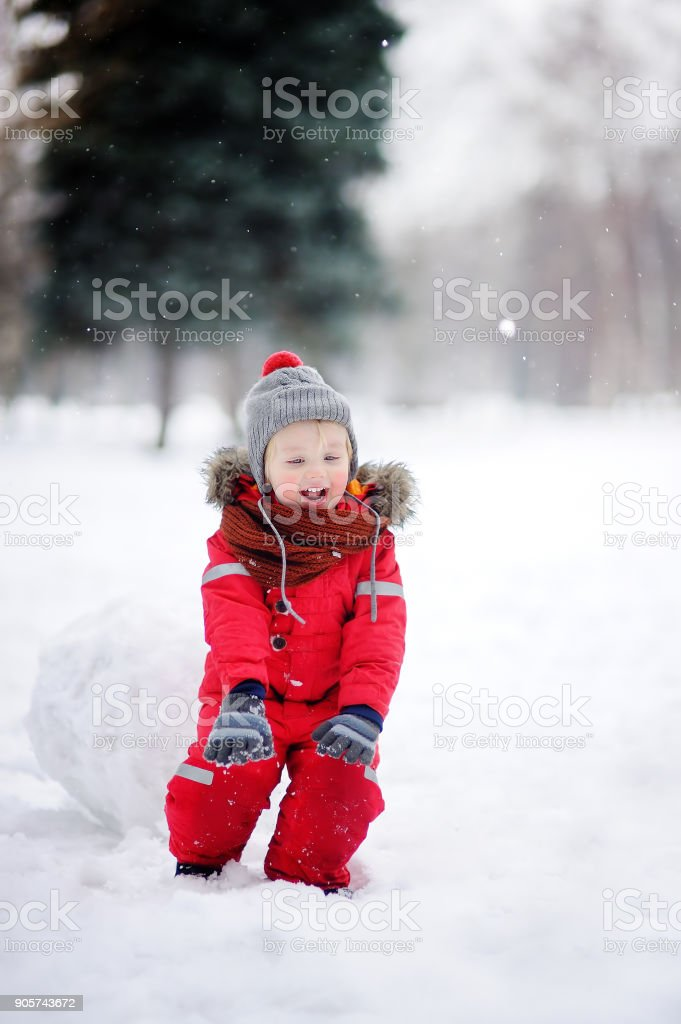 Little boy in red winter clothes having fun with snowball stock photo