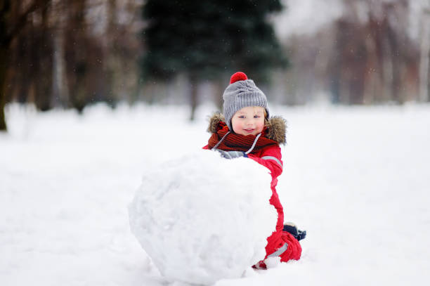 kleiner junge in rote winterkleidung spaß mit schneemann - schneemann bauen stock-fotos und bilder