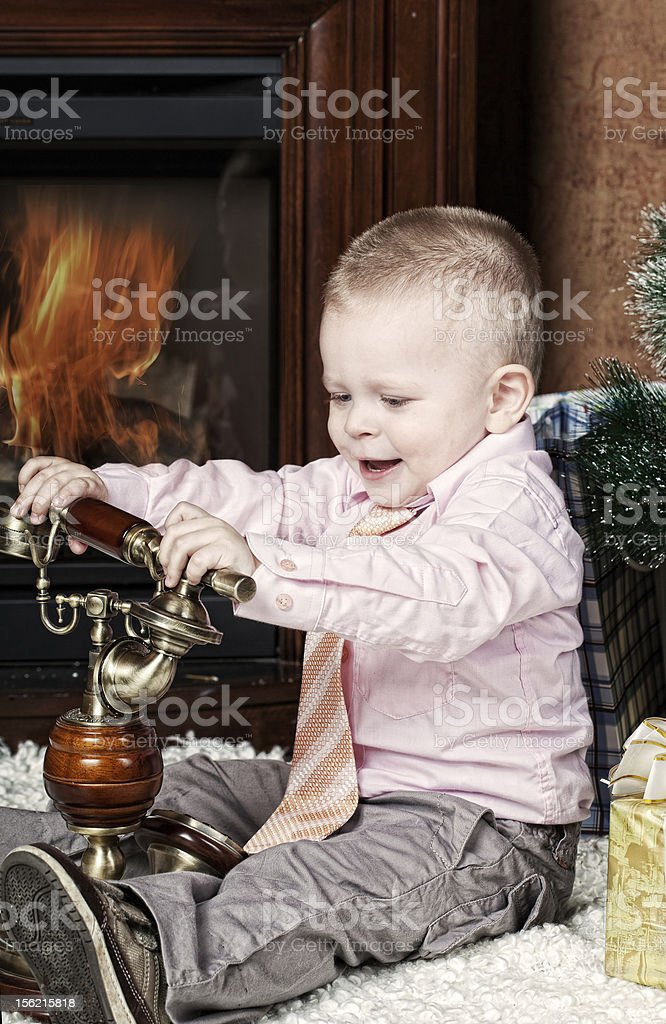 little boy in  room with  fireplace sits at  Christmas fur-tree royalty-free stock photo